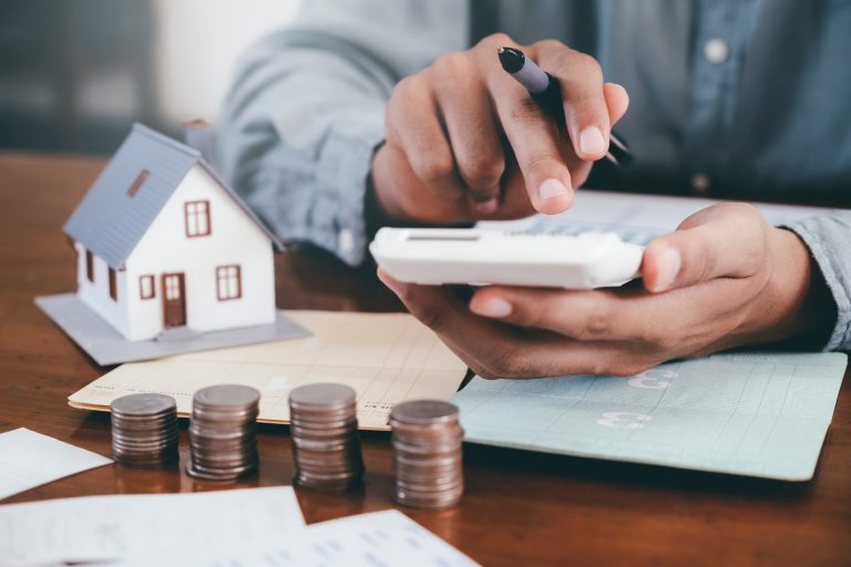 Businessman is Savings money and calculating.Save money for home cost